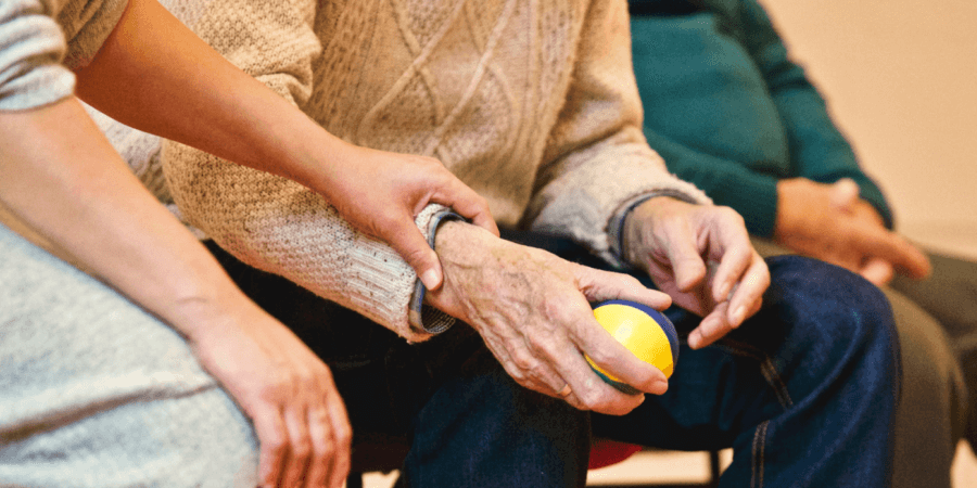 Old man holding a ball with a nurse's hand on his arm