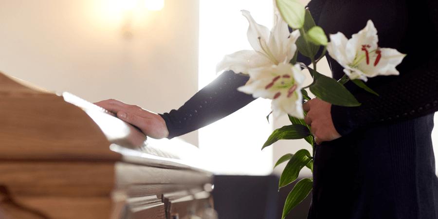 Persona tocando un ataud mientras carga flores